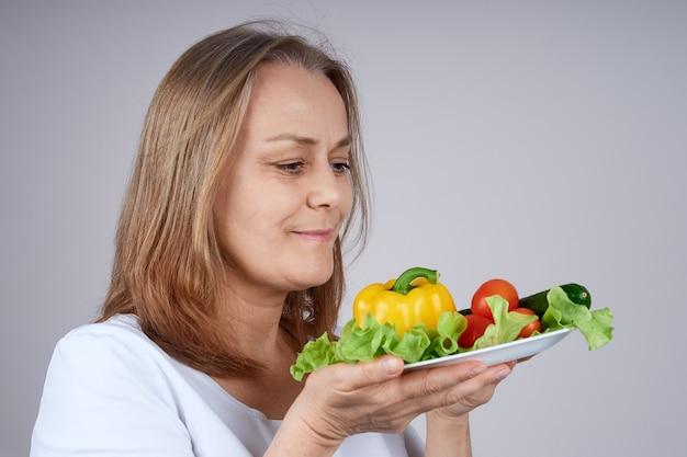 Senior woman in a white shirt détient une assiette de légumes, se dresse de profil.