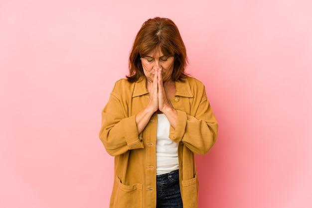 Senior woman isolated priant, montrant la dévotion, personne religieuse à la recherche d'inspiration divine