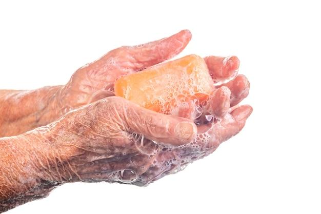 Senior woman laver les mains à l'aide de savon blanc, concept d'hygiène