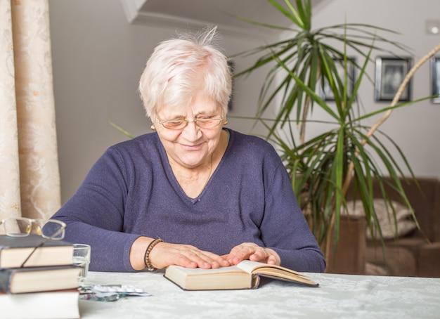 Senior woman lit concentré dans un livre dans la bibliothèque de la maison de retraite