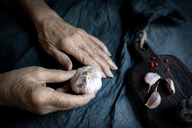 Senior woman mains avec une tête d'ail