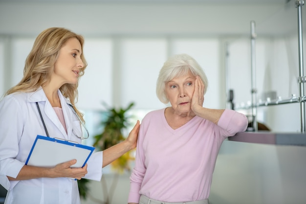 Senior woman parler avec le médecin et à la frustration