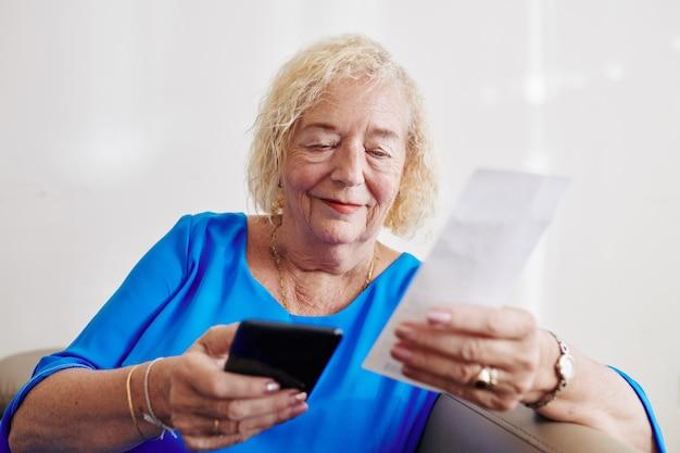 Senior woman payer les factures en ligne