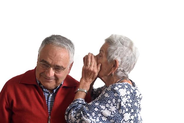 Senior woman raconte un secret à un vieil homme sur fond blanc