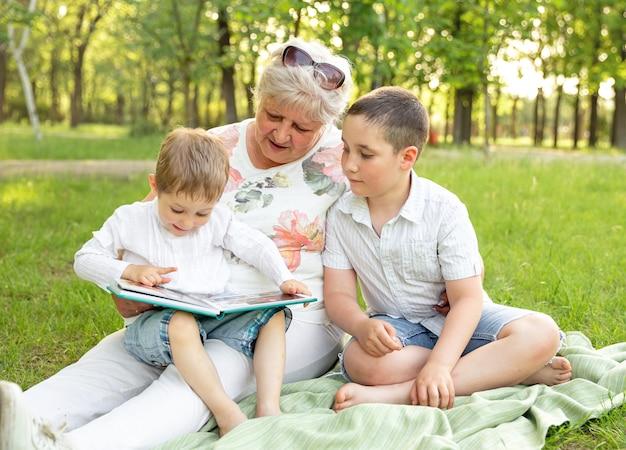 Senior woman reading book pour ses petits-enfants.