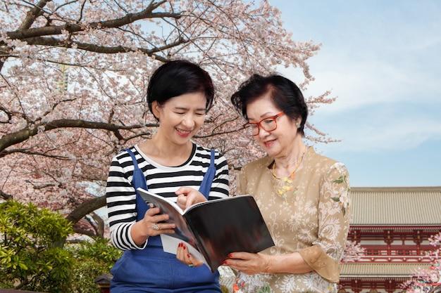 Senior woman reading a travel guidebook avec sa fille