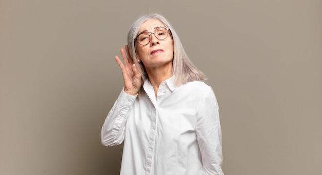Senior woman à la recherche sérieuse et curieuse, à l'écoute, en essayant d'entendre une conversation secrète ou des potins, écoute clandestine