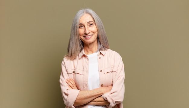 Senior woman ressemblant à un accomplisseur heureux, fier et satisfait souriant avec les bras croisés