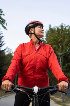 Senior woman riding bike à l'extérieur