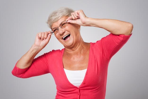Senior woman s'amuse avec des lunettes de mode