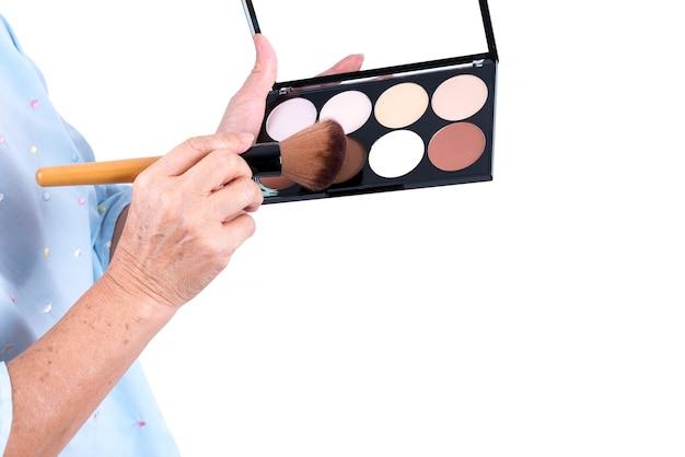 Senior woman's hand holding brush et cosmétiques professionnel 8 nuances contour visage power foundation maquillage palette isolé sur fond blanc