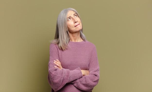 Senior woman se sentir heureux, fier et plein d'espoir, se demander ou penser, en levant pour copier l'espace avec les bras croisés