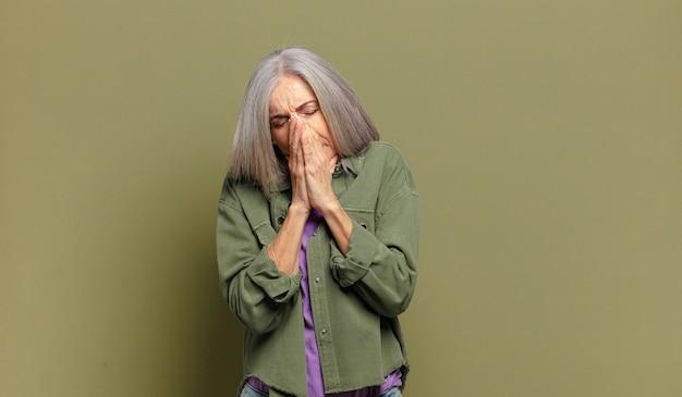 Senior woman se sentir inquiet, plein d'espoir et religieux, priant fidèlement avec les paumes pressées, implorant pardon