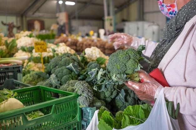Senior woman sélectionnant le brocoli au marché fermier local. choix de légumes frais et crus. femme avec des gants de protection et un masque