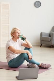 Senior woman sitting on the floor sur un tapis d'exercice et de l'eau potable après une formation en ligne à la maison