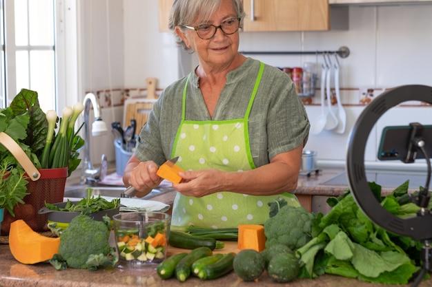 Senior woman streaming leçon de cuisine végétarienne en ligne. table de cuisine à la maison pleine de légumes