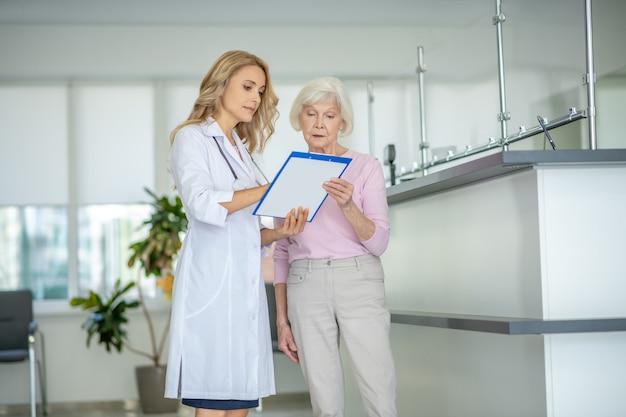 Senior woman talking avec le médecin et l'air inquiet