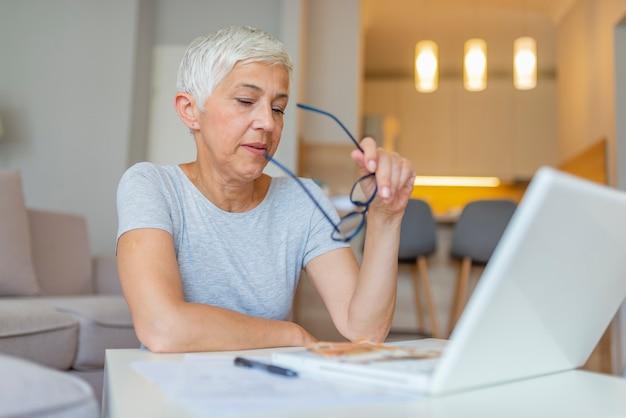 Senior woman travaillant sur le financement de la maison.