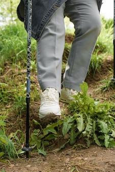 Senior woman trekking dans la nature. une femme âgée descend la colline à l'aide de bâtons de marche. gros plan sur des bottes, en descendant. randonnée, concept de mode de vie actif