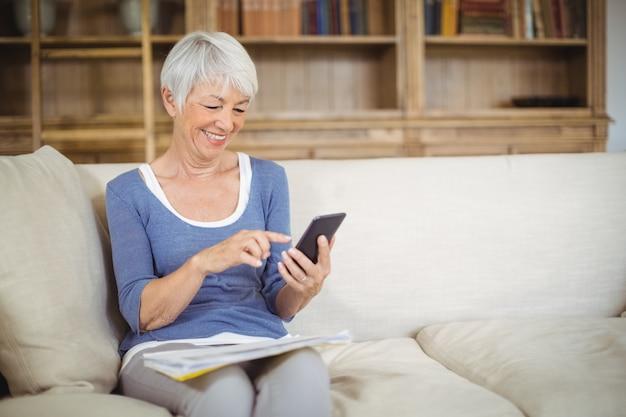 Senior woman using mobile phone dans la salle de séjour