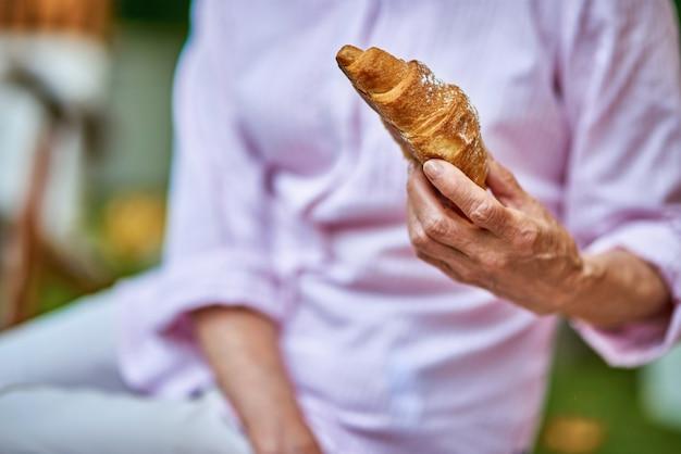 Senior woman va prendre le petit déjeuner avec un croissant