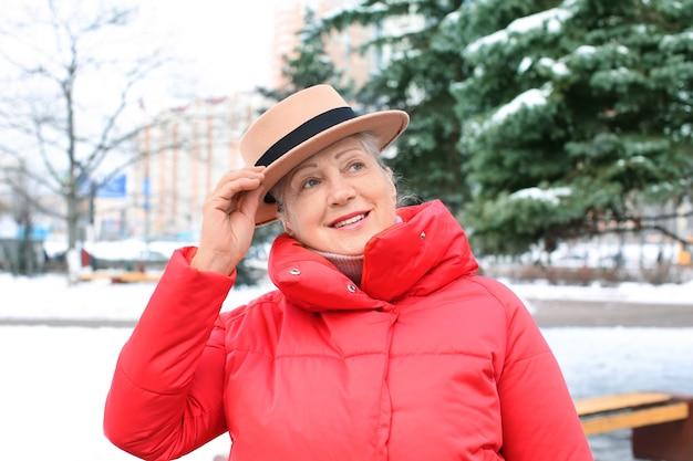 Senior woman en vêtements chauds à l'extérieur. vacances d'hiver
