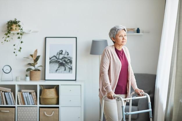 Senior woman walking autour de la pièce avec l'aide de marcheur, elle est à la maison