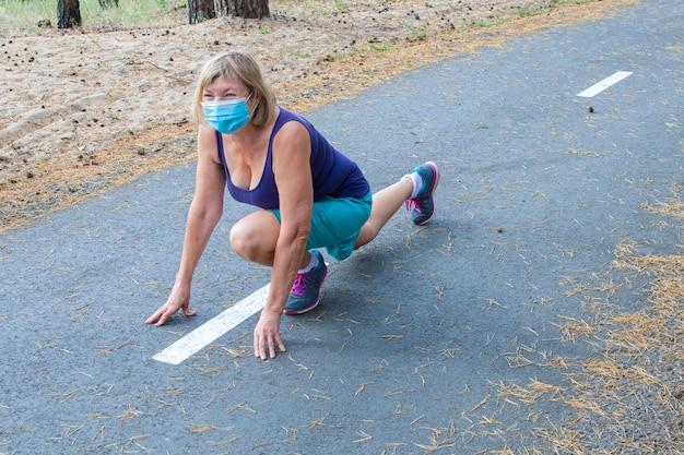 Senior woman wearing a medical mask est runn dans une position de départ à l'extérieur dans le parc