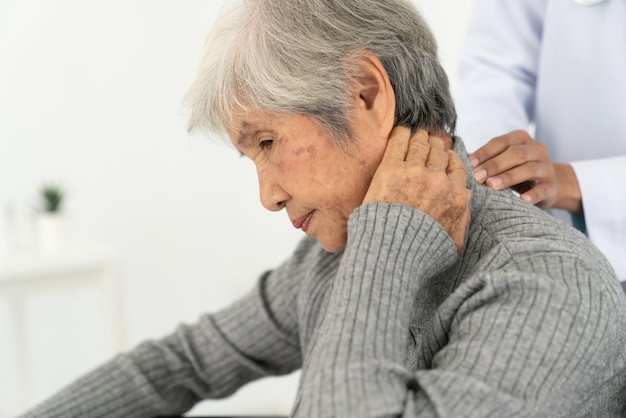 Senior woman with neck pain in the medical office, sick senior woman with back cou et épaules douleur sur l'articulation et les muscles.