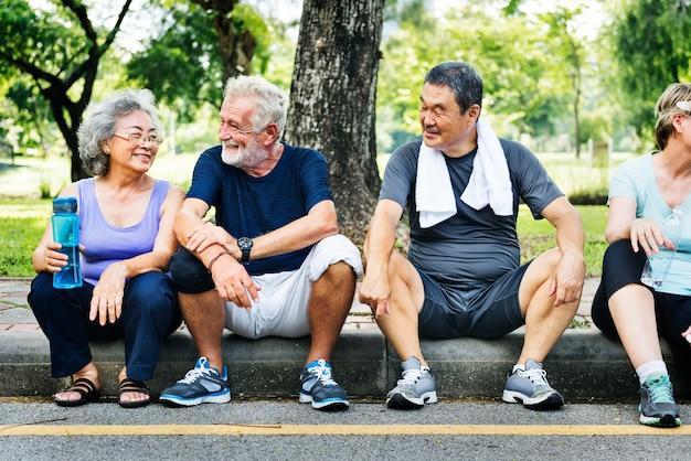 Seniors assis dans le parc après une séance d'entraînement
