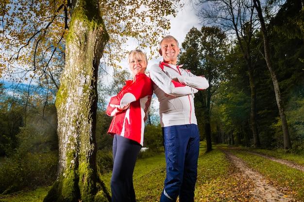 Seniors entraînement sportif sur une route forestière