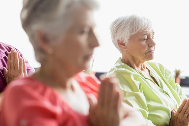 Seniors faisant du yoga avec les yeux fermés