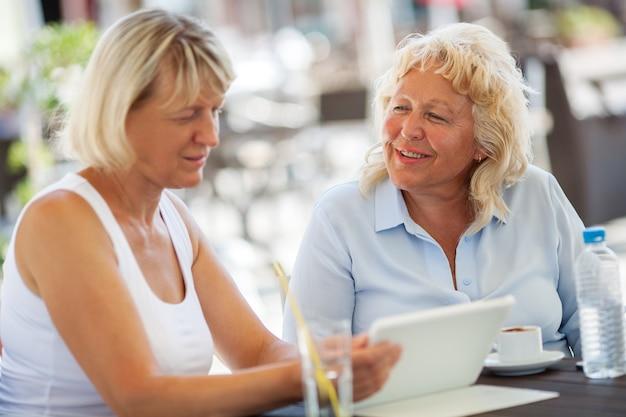 Seniors femmes passer du temps avec pad dans le café en plein air
