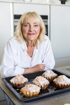 Seniorwoman souriant s'appuyant sur une table avec plateau de cuisson