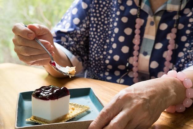Senoir aîné mangeant un gâteau au fromage de myrtille au café.