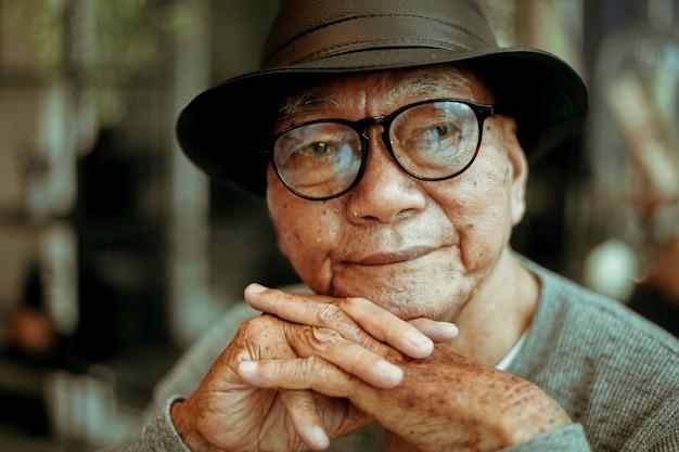 Senoir asiatique vieux retraité boire un café au café sourire et visage heureux