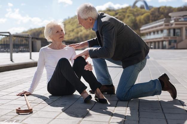 Senor femme inquiète à la mode ayant mal et attendant de l'aide tandis que l'homme bon recommande