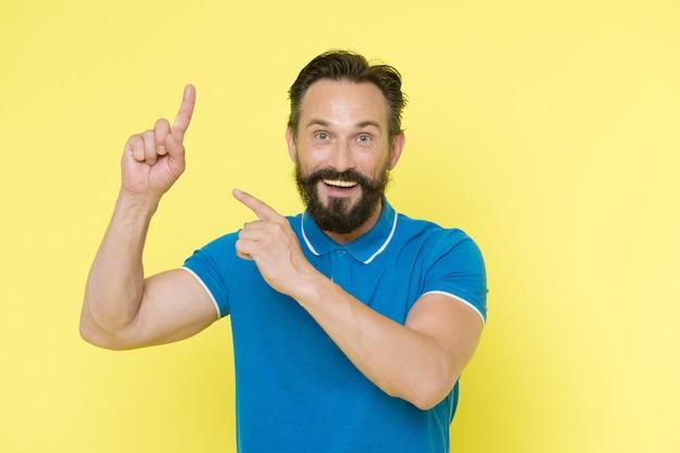 Sens de pointage. homme pointant l'index fond jaune. guy barbe et moustache montre la direction. regardez cette publicité. idée fraîche gaie d'homme barbu. vérifiez-le.