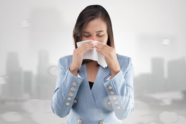 Sensation de brûlure du nez de femme d'affaires en raison de la fumée toxique et des particules dans l'air