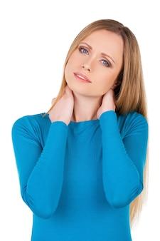 Sensation de douleur dans le cou. jeune femme déprimée touchant son cou et regardant la caméra en se tenant debout isolée sur blanc