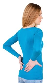 Sensation de douleur dans le dos. vue arrière de la jeune femme tenant les mains sur le dos et regardant loin en se tenant debout isolé sur blanc