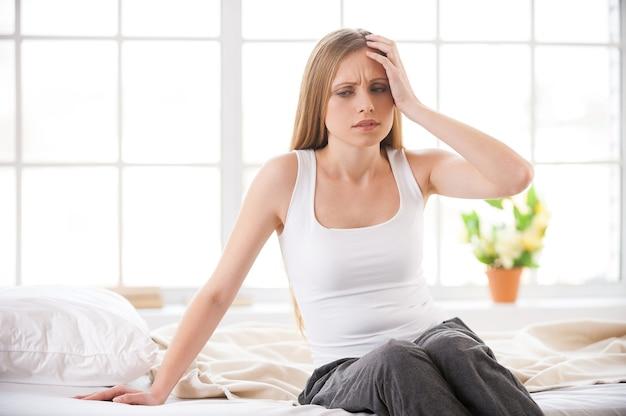 Sensation de mal de tête. jeune femme frustrée touchant la tête avec la main et exprimant la négativité alors qu'elle était assise dans son lit dans son appartement