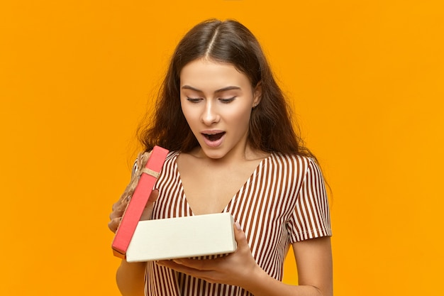Sensationnel. photo de studio d'une jeune femme européenne émotive étonnée boîte d'ouverture avec cadeau