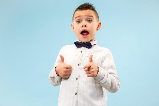 Sensationnel. portrait avant demi-longueur mâle attrayant sur fond bleu studio. jeune garçon adolescent surpris émotionnel debout avec la bouche ouverte. émotions humaines, concept d'expression faciale. couleurs tendance