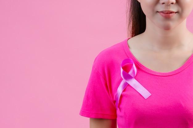 Sensibilisation au cancer du sein, femme en t-shirt rose avec ruban rose satiné sur la poitrine, favorisant la sensibilisation au cancer du sein