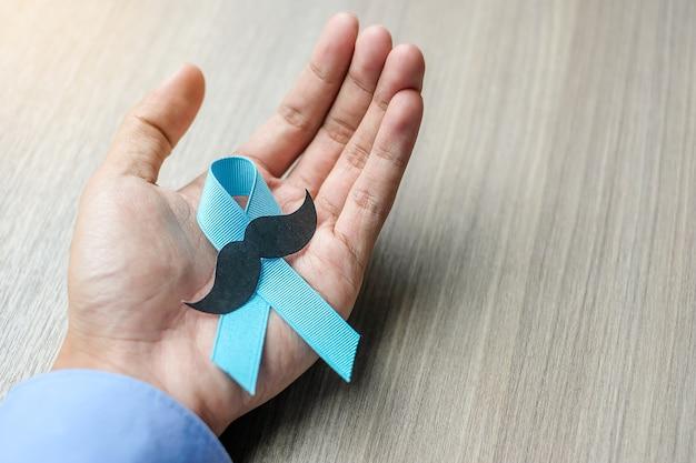 Sensibilisation au cancer de la prostate, homme tenant un ruban bleu clair avec moustache