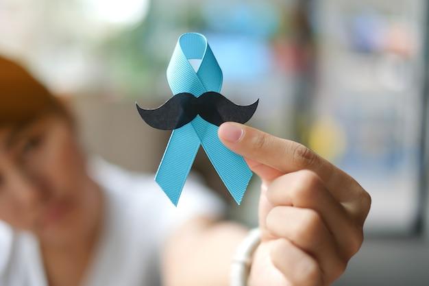 Sensibilisation au cancer de la prostate, main de femme tenant un ruban bleu clair