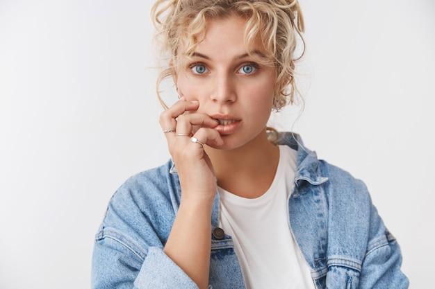Sensualité, concept de style de vie de tendresse. jolie petite amie blonde aux yeux bleus et rêveuse, coupe de cheveux bouclés, bouche ouverte, regardant la caméra, regardant la caméra, lèvre réfléchie, pensant écouter attentivement, s'inquiéter