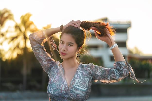 Sensualité femme asiatique avec des cheveux de queue de cheval sur le côté de la plage