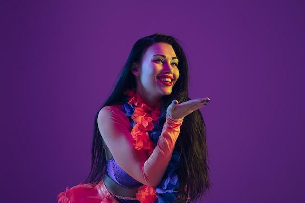 Sensuel, baiser. modèle brune hawaïenne sur mur violet en néon. belles femmes en vêtements traditionnels souriant et s'amusant. vacances lumineuses, couleurs de célébration, festival.